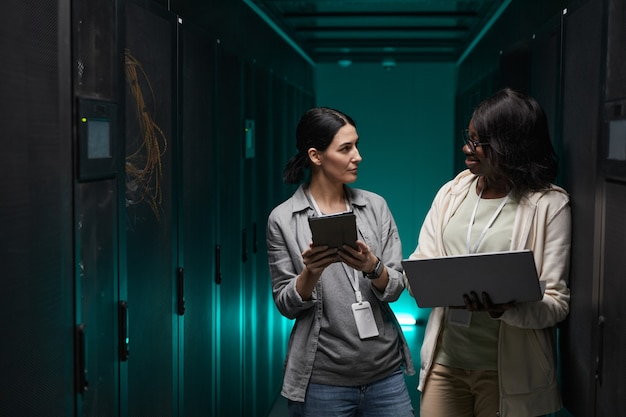 Waist up portrait of two young women using laptop while working with supercomputer in server room, copy space