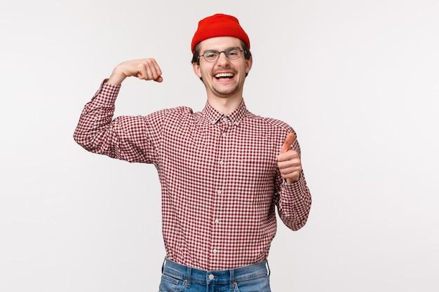上半身の肖像画、赤いビーニー、メガネの幸せで陽気な男は、親指を立て、上腕二頭筋を屈曲させ、体に自信を持っていることを示しています。