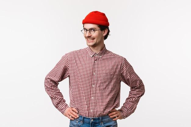 赤いビーニーとメガネ、チェックシャツ、自信を持ってまっすぐなポーズで準備ができて立っている腰と手をつないでカメラを笑顔で上向きの肖像画明るいと熱狂的な若いヒップな男