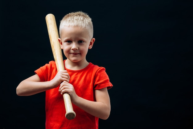 Waist up portrait view of the cute little boy baseball player holding bat and looking at the camera. isolated on black background. childhood and sport concept