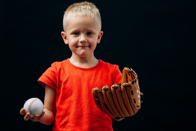 Waist up portrait view of the cute little boy baseball player wearing special glove holding ball and looking at the camera. isolated on black background. childhood and sport concept