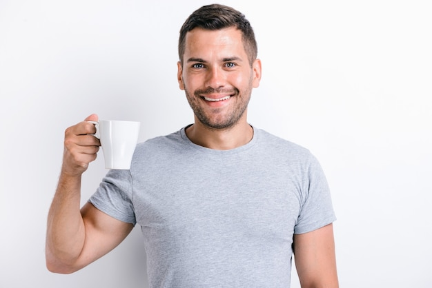 Waist up portrait view of the handsome man standing and holding a cup of morning tea or coffee and smiling while looking at the camera. stock photo