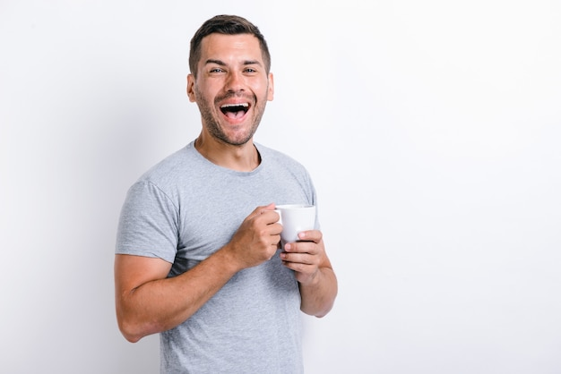 Waist up portrait view of the happy caucasian man standing and rejoicing with the cup of coffee. morning beverages concept. stock photo