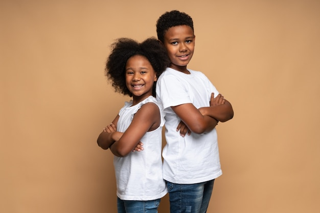 Waist up portrait view of the lovely multiracial brother and sister standing back to back to each other and smiling while posing at the studio over the beige wall
