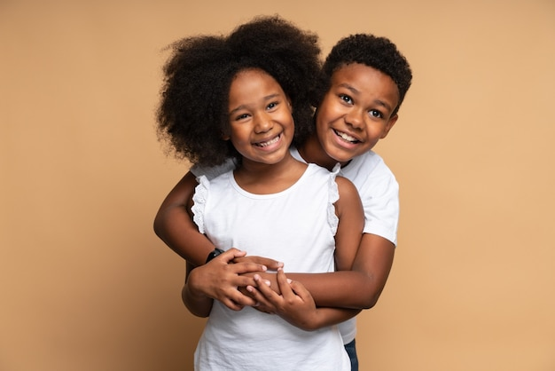 Waist up portrait view of the lovely multiracial girl looking at the camera with cheery smile while her brother embracing her with tenderness. family relationships concept