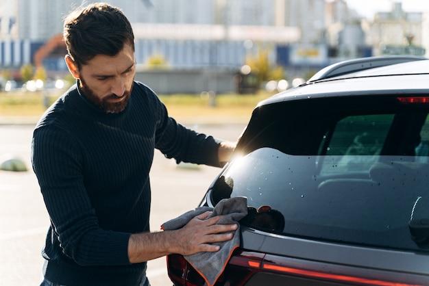 화창한 여름날 거리에서 시간을 보내는 동안 새 차 뒤를 청소하는 만족한 집중된 남자의 허리 초상화. 스톡 사진