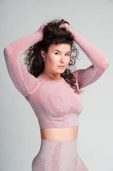 분홍색 스포츠를 입은 사려깊은 백인 여성 조깅하는 사람의 허리 초상화는 그녀의 머리를 손으로 잡고 흰 벽 배경에 포즈를 취합니다.