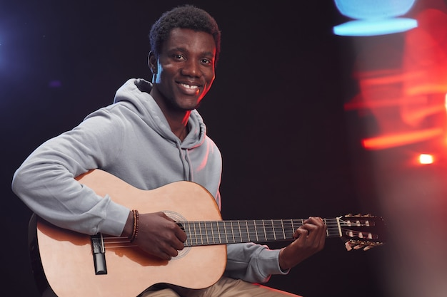 Waist up portrait of young african-american man playing acoustic guitar on stage and smiling happily, copy space