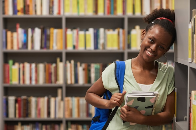 Waist up portrait of young africanamerican woman standing in school library and smiling at camera co...