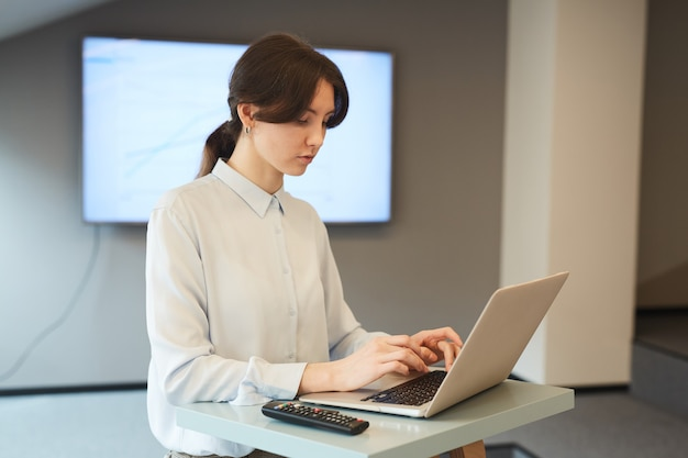 Waist up portrait of young businesswoman typing on laptop keyboard while working at standing table in minimal grey office interior, copy space