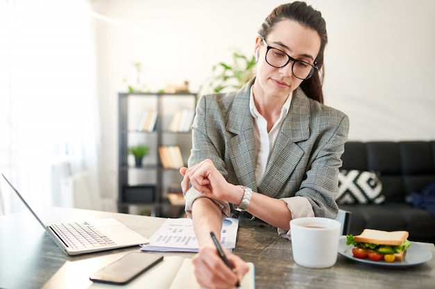 Waist up portrait of young contemporary businesswoman working in office, copy space