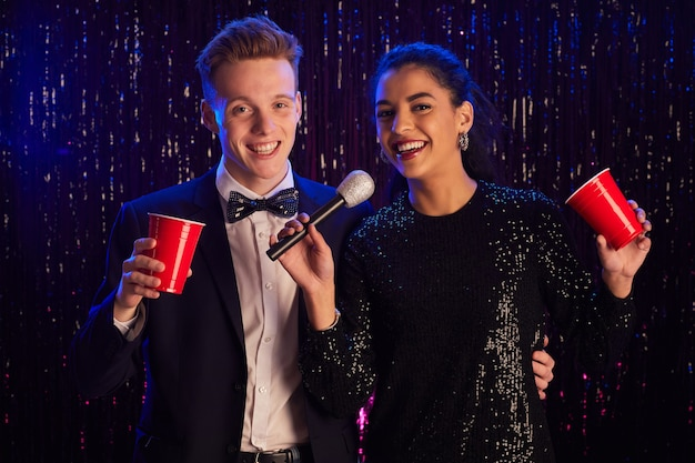 Waist up portrait of young couple holding microphone and smiling at camera while enjoying karaoke party
