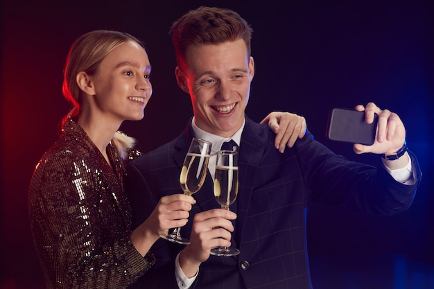 Waist up portrait of young couple taking selfie photo via smartphone while enjoying party at prom night standing against lack background