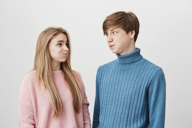 Waist up portrait of young female and male wearing knitted colourful sweaters having discontent looks pouting cheeks