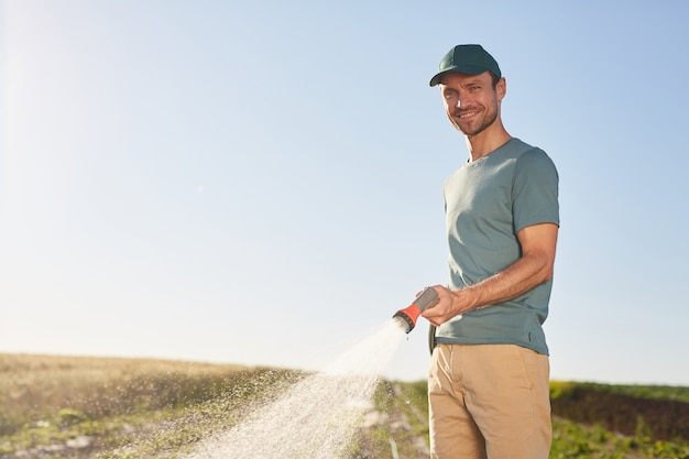 Waist up portrait of young male worker watering crops at vegetable plantation and smiling at camera while standing outdoors against blue sky, copy space
