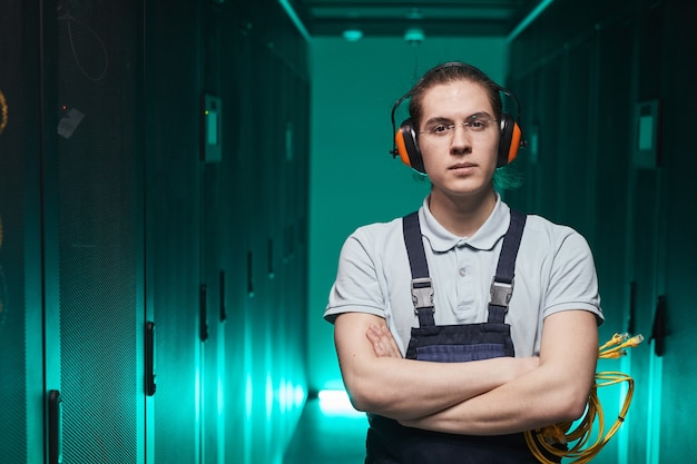 Waist up portrait of young network technician looking at camera while standing with arms crossed in server room, copy space