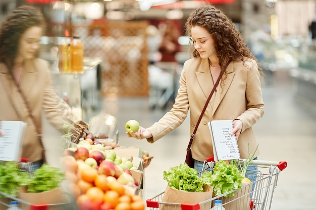Waist up portrait of young woman choosing fresh organic fruits while buying groceries at farmers market or supermarket