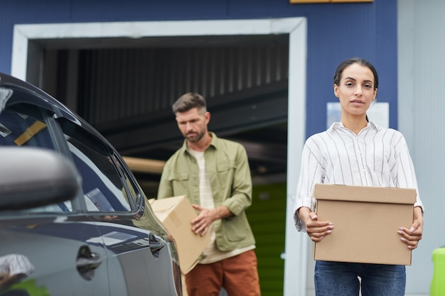 Waist up portrait of young woman holding box and  while standing by car in self storage facility, copy space