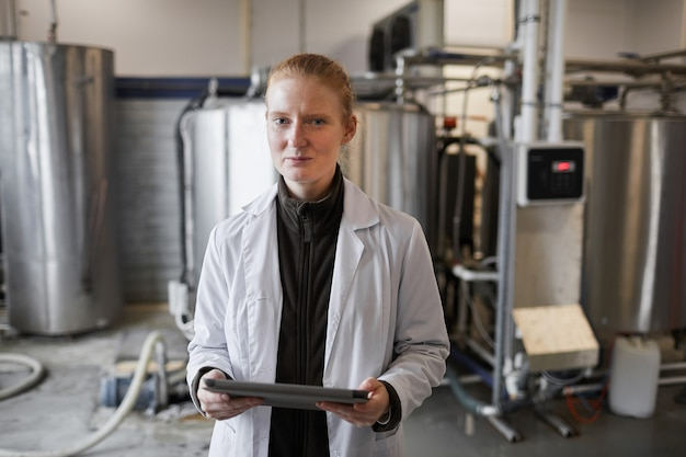Waist up portrait of young woman wearing lab coat posing against machines while working at dairy factory, copy space