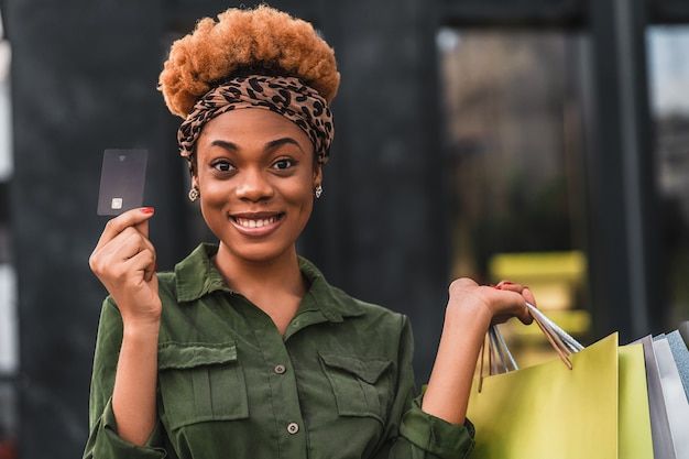 Waist up of pretty afro american female going to shopping with a credit card while standing with shopping bags outdoors