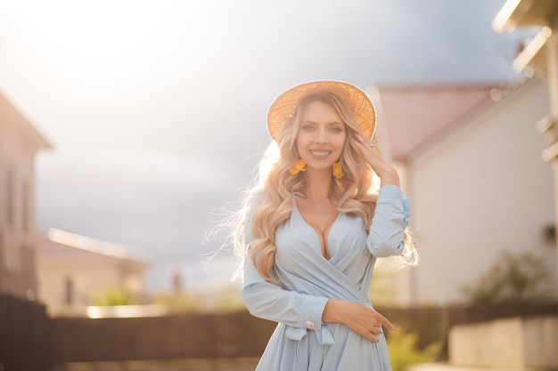 Waist up of pretty young woman wearing summer dress and straw hat while walking on city street. beauty and fashion concept