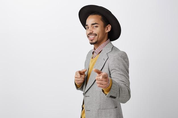Mezzo busto di sasssy fiducioso imprenditore afro-americano che punta le dita, complimenti, gesto ben fatto