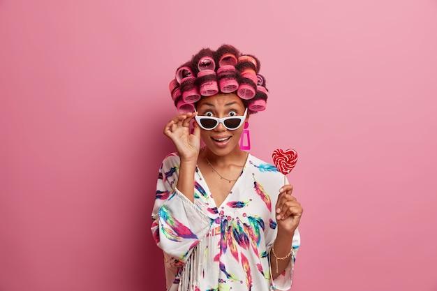 La vita in su di una donna etnica stupita tiene la mano sugli occhiali da sole, non riesce a credere ai suoi occhi, indossa una vestaglia domestica casual, tiene in mano il lecca-lecca, indossa i bigodini, ha un aspetto glamour, posa al coperto a casa