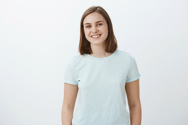 Waist-up shot of ambitious happy and cute female brunette in trendy t-shirt smiling joyfully being delighted and pleased while receiving congratulations for winning award over white wall