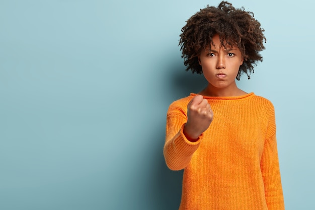 Waist up shot of annoyed woman with afro haircut, shows fist, looks angrily, threatens about revenge, wears casual orange jumper, isolated over blue wall with empty space. listen to me
