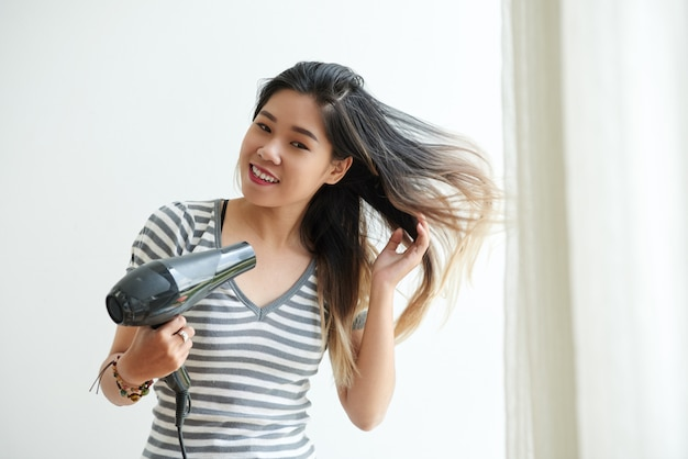 Waist up shot of asian girl blow-drying her hair at home