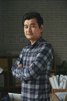 Waist up shot of asian man standing arms folded in an architect office