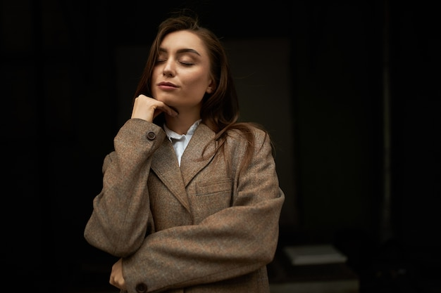 Waist up shot of attractive fashionable young european female with long brown hair posing isolated keeping eyes closed, having dreamy peaceful facial expression, wearing mens jacket, smiling