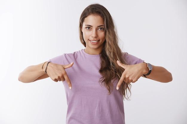 매력적인 건강한 현대 성인 여성이 검지 손가락을 아래로 가리키며 흥미로운 좋은 프로모션, 복사 공간, 광고 흰 벽을 보여주는 제안을 하는 허리 위로 샷