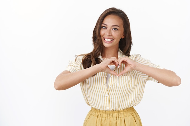 Waist-up shot attractive romantic young girlfriend confess in love, show heart sign and smiling toothy, adore partner making surprise, telling about feelings and affection