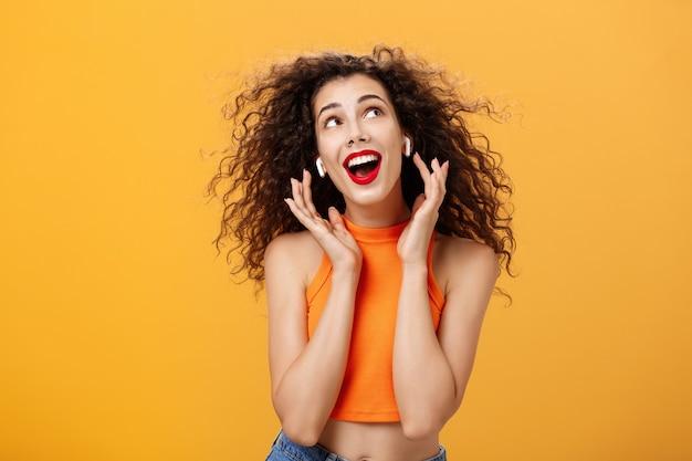 Colpo in vita di una donna europea dai capelli ricci sciocca e attraente in top corto usando auricolari wireless che toccano gli auricolari e guardano nell'angolo in alto a destra deliziati e spensierati sul muro arancione.