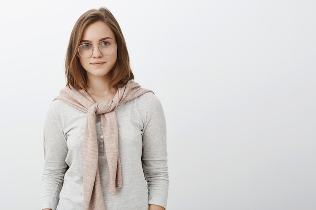 Waist-up shot of attractive stylish hipster girl in glasses and sweatshirt on shoulders smiling self-assured working on new project standing confident and assured over gray wall