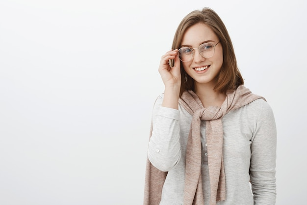 Waist-up shot of attractive stylish young woman in glasses and pink pullover tied over neck wearing blouse touching eyeglasses and smiling friendly hanging out in unfamiliar company