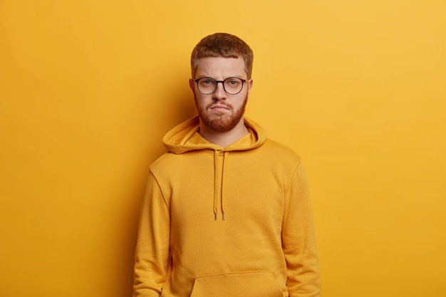 Waist up shot of bearded ginger man looks directly , has strict confident expression, wears spectacles and hoodie, student comes on lecture in university, isolated on yellow wall