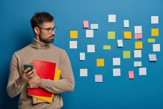 Waist up shot of bearded man has creative thinking, colorful memo pads stuck on blue wall, holds spiral notepad