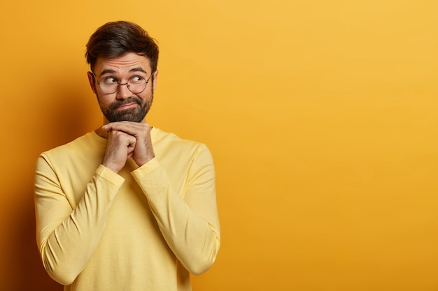 Waist up shot of bearded young man thinks seriously about your offer, keeps hands under chin, concentrated aside, wears optical glasses and sweater, dreams about something, isolated on yellow wall