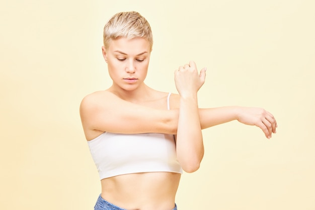 Waist up shot of beautiful fashionable young woman with boyish haircut having concentrated look, being focused on her feelings while stretching arm muscles, pressing shoulder and elbow to her chest