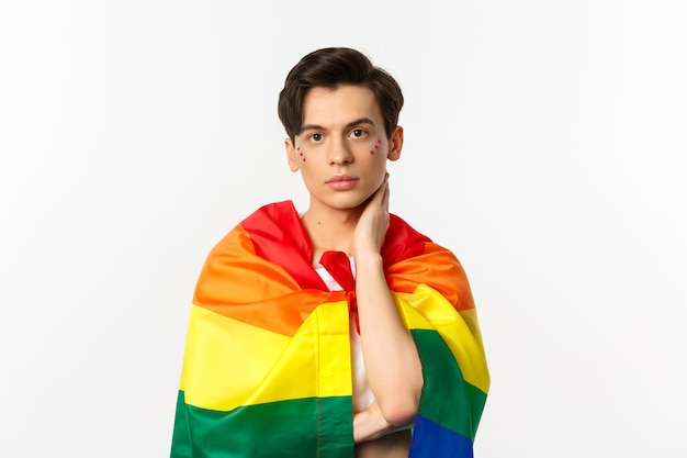 Waist-up shot of beautiful gay man with glitter on face, wrap himself with rainbow lgbt flag and touching face gently, looking at camera, white.