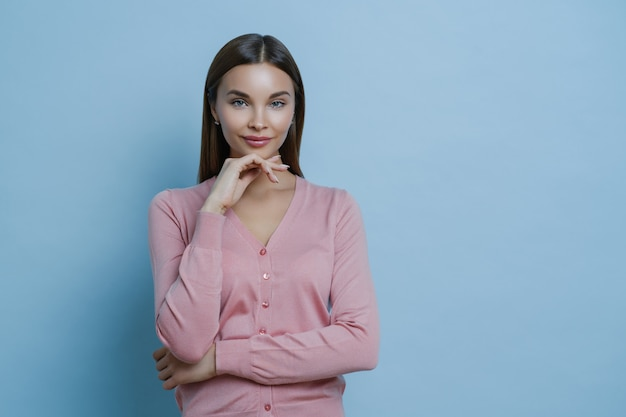 Waist up shot of beautiful young european woman keeps hand under chin, looks directly at camera
