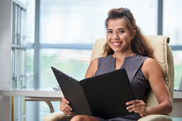 Waist up shot of business lady studying documentation while seated in her office chair