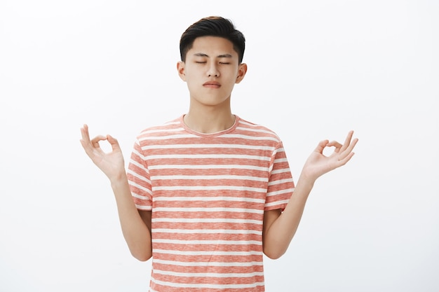 Waist-up shot of calm focused attractive asian male student taking control of thoughts, standing in lotus pose with zen gesture, meditating restoring energy with yoga
