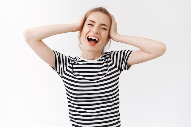 Беззаботная, живая, эмоциональная молодая женщина с растрепанной булочкой в полосатой футболке, улыбающаяся, поющая и наслаждающаяся прекрасным днем, чувствующая себя расслабленной и радостной, чувствуя себя расслабленной и счастливой, танцующая касание головы, белый фон