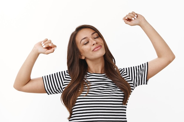 Waist-up shot carefree relaxed cute lazy girl stretching hands up, waking up energized, sleep well, close eyes and smiling delighted, enjoy weekends, standing in striped t-shirt white wall