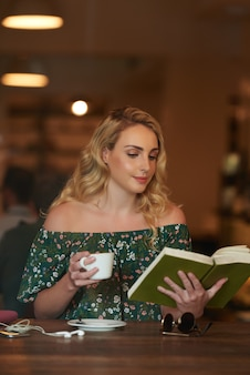 Waist up shot of carefree woman reading a book in a coffee shop