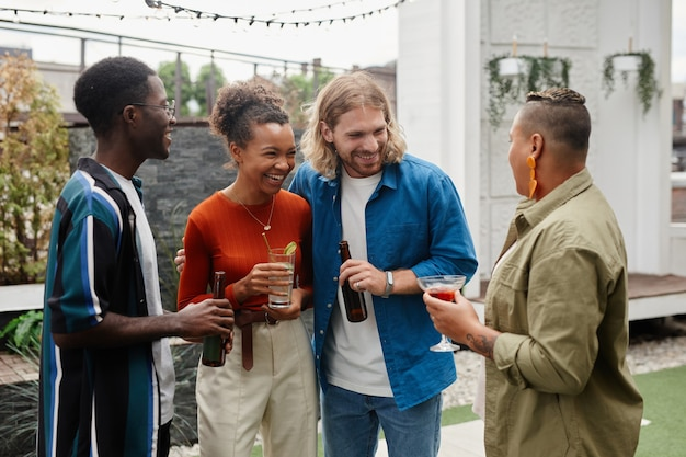 Waist up shot of carefree young people drinking beer while enjoying outdoor party with friends