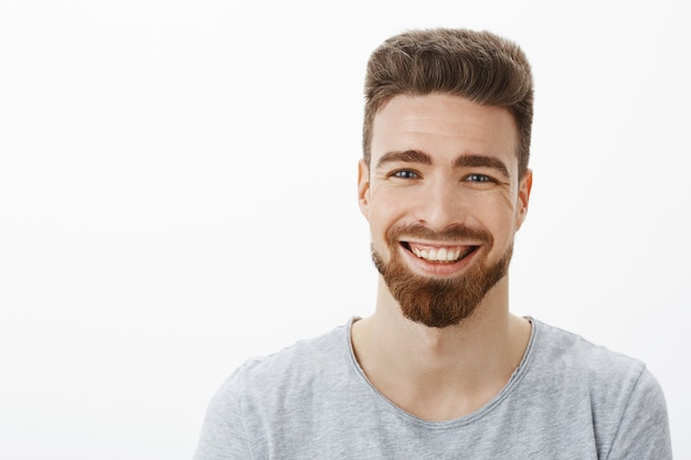 Waist-up shot of charming carefree and optimistic handsome man with beard, moustache and cute blue eyes laughing joyfully squinting from joy and amusement having fun against gray wall
